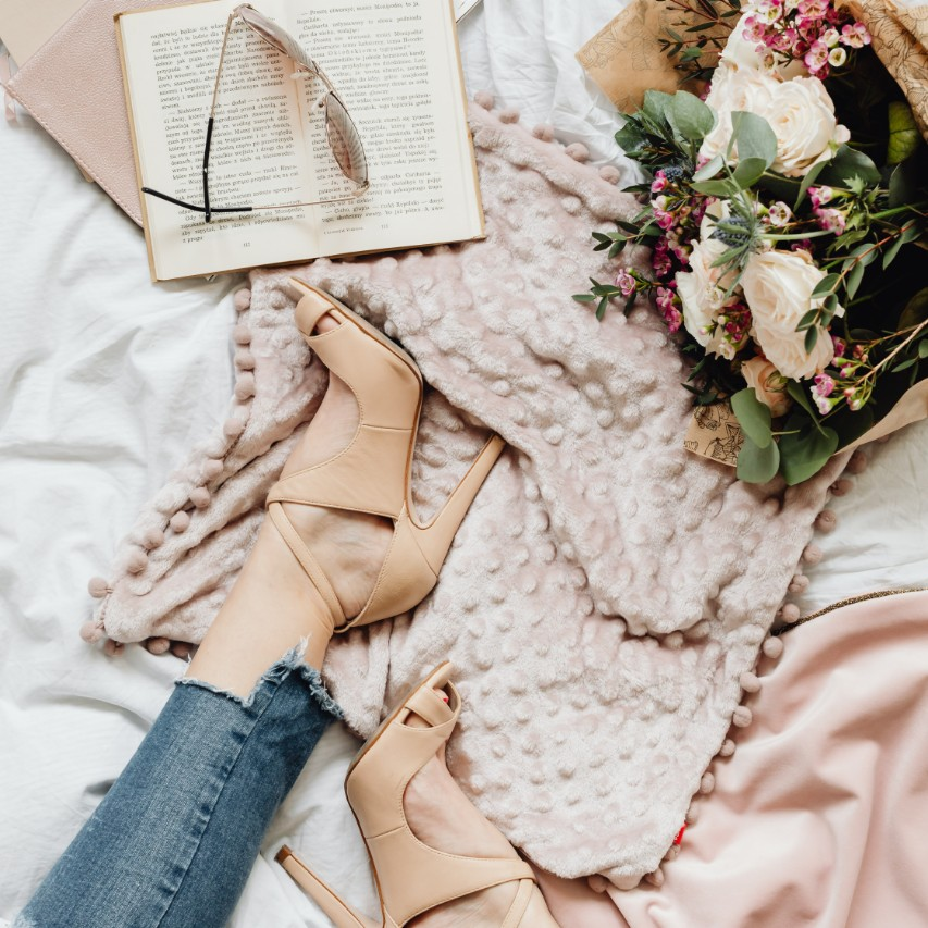 weekend hotlist light pink shoes flowers book and sunglasses sitting on a bed