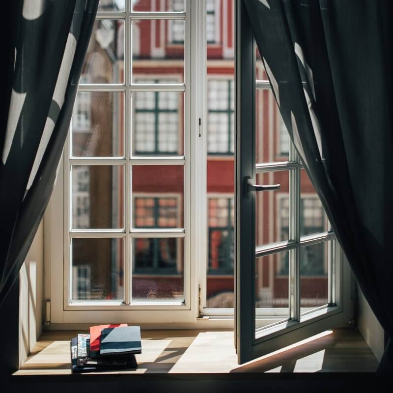 View out of an open window with books on the windowsill to represent focus and success