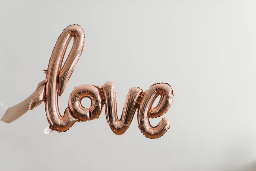 find lasting love - person holding a rose gold balloon made of the letters spelling love